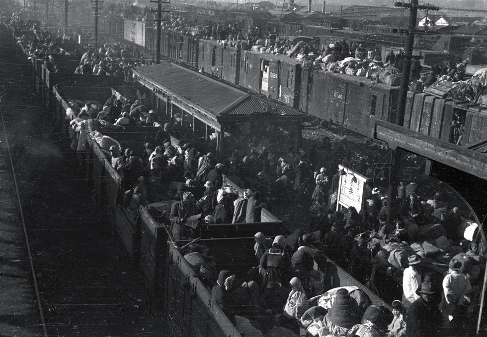 A soldier stands in a crowd as refugees try to get on a train at Daegu Station on Dec. 29, 1950. ICRC via Yonhap