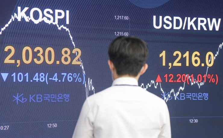 A dealer stands in front of an electronic trading board on the trading floor of KB Kookmin Bank in Yeouido, Seoul, June 15. Korea Times file
