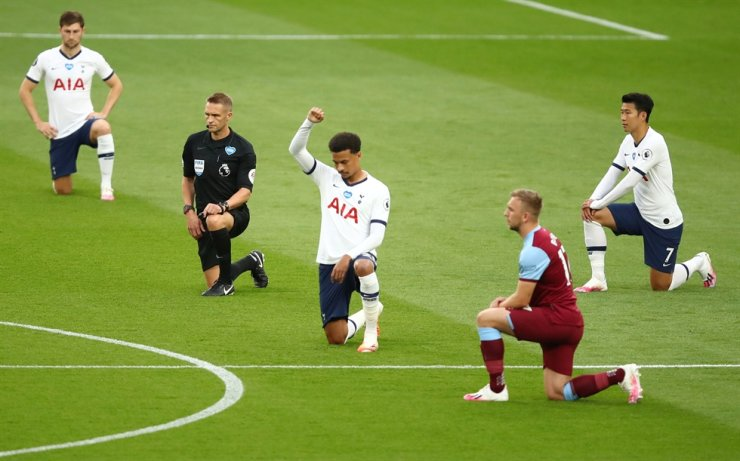Tottenham Hotspur's Dele Alli, center, kneels with other players in support of the Black Lives Matter campaign before the match between Tottenham and West Ham at the Tottenham Hotspur Stadium in London, Tesday, as play resumes behind closed doors following the outbreak of the coronavirus disease (COVID-19). / Reuters-Yonhap