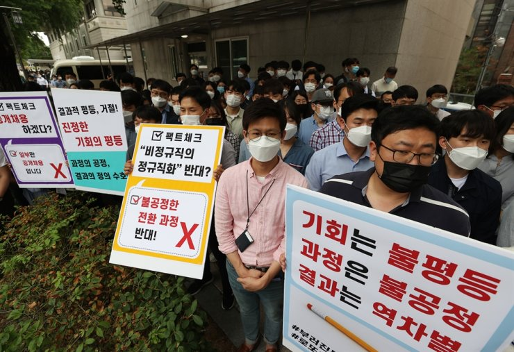 Members of Incheon International Airport Corp.'s union hold up signs opposing the state-run firm's plan to directly hire contract security workers, as part of a protest against the move in front of Cheong Wa Dae, Thursday. / Yonhap