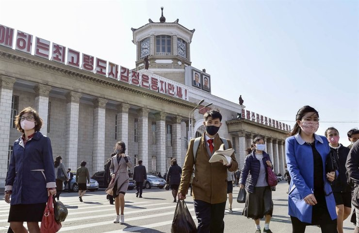 People wearing protective face masks walk amid concerns over the new coronavirus disease (COVID-19) in front of Pyongyang Station in Pyongyang, North Korea, April 27, 2020, in this photo released by Kyodo. Kyodo via Reuters