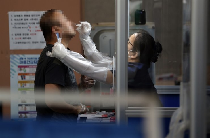 A citizen gets a virus test at a makeshift clinic set up at Gwanak public health center in Seoul, Monday. Yonhap