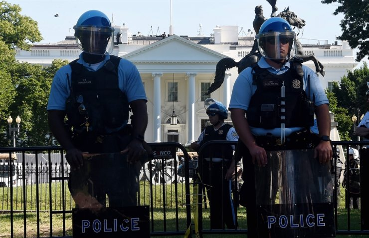 Police hold a perimeter near the White House as demonstrators gather to protest against the killing of George Floyd. (Photo by Olivier DOULIERY / AFP)