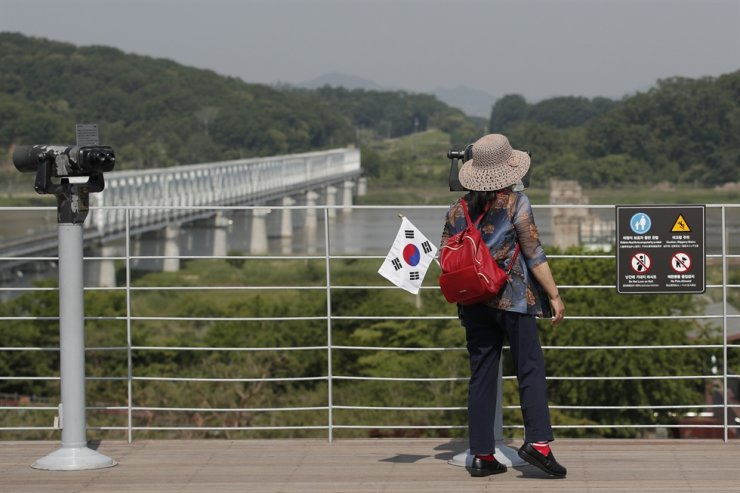 A visitor carrying a South Korean flag uses binoculars to view the northern side at the Imjingak Pavilion in Paju, South Korea, Tuesday, June 9, 2020. North Korea said Tuesday it will cut off all communication channels with South Korea as it escalates its pressure on the South for failing to stop activists from floating anti-Pyongyang leaflets across their tense border. AP