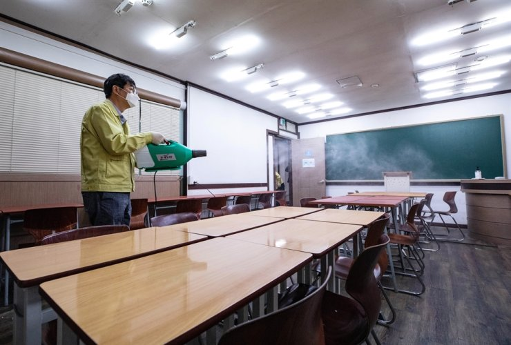quarantine official disinfects a classroom at a private cram school in Mokdong, Seoul, Monday, after a family member of a high school student, who studied at a private institute in the region, tested positive for COVID-19 the previous day. Yonhap