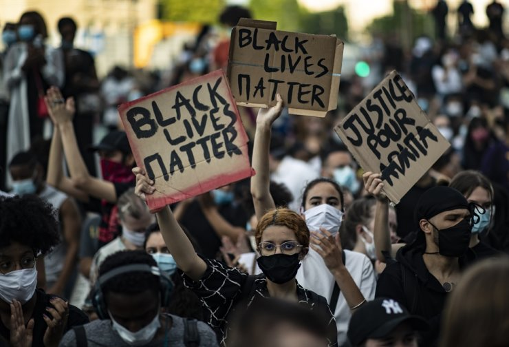 Protesters wearing a protective face masks hold placards inscribed 'Black Lives Matter' as they take part in a demonstration to protest in support of the George Floyd protests in the United States, and also to commemorate a similar circumstance in France when Adama Traore, a 24 year old old black Frenchman who was killed in 2016 by police, during an illegal rally in front of the new courthouse in Paris, France, 02 June 2020. EPA-Yonhap
