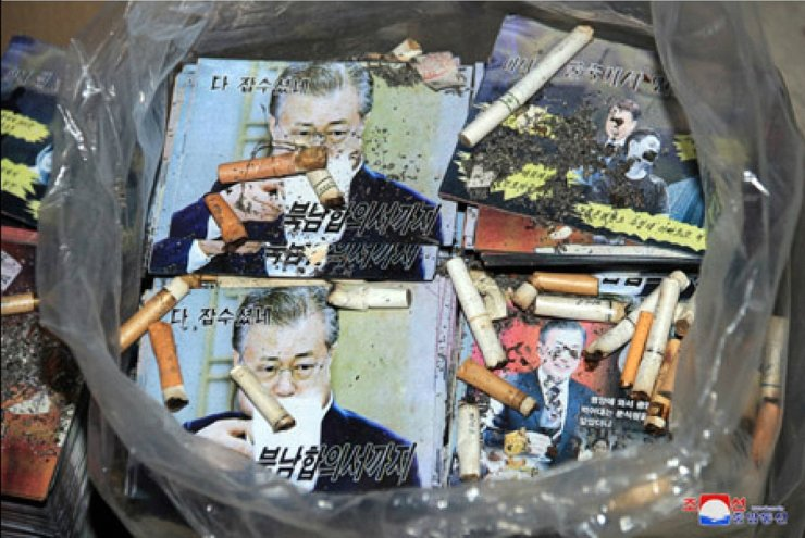 This captured image from the Korean Central News Agency website shows photos of President Moon Jae-in imprinted on anti-South Korea leaflets being covered with cigarette butts and dirt. Yonhap