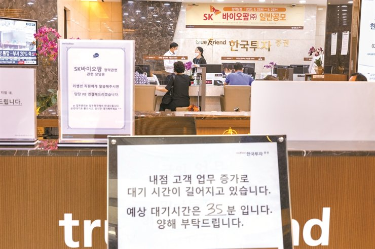 A sign at a Seoul branch of Korea Investment and Securities says at least 35-minute wait time is expected before being tended to due to a spike in the number of customers on the last day of request filings needed for subscription to purchase shares of SK Biopharmaceuticals ahead of the firm's initial public offering, June 24. Korea Times file