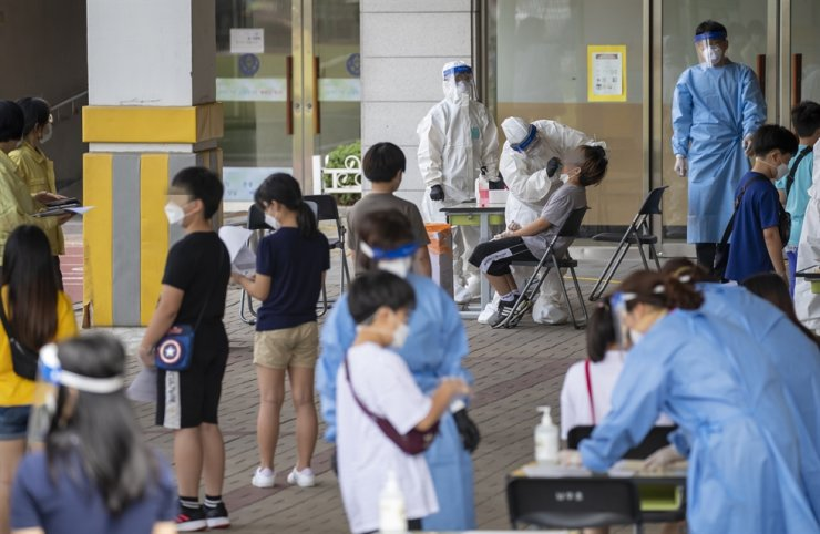 Students at Nanwoo Elementary School in Seoul's Gwanak District receive COVID-19 testing at the school, Sunday, after a part-time teacher there tested positive for the virus. The teacher's case was traced to an infection cluster that recently occurred at a church in the district. / Yonhap