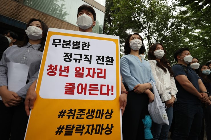 Members of a union of the Incheon International Airport Corp. hold a sign, which reads