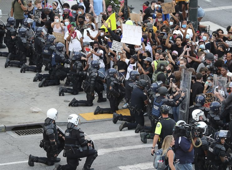 In a show of peace and solidarity, law enforcement officials with riot shields take a knee in front of protesters on Monday, June 1, 2020, in Atlanta, during a fourth day of protests over the death of George Floyd. /AP