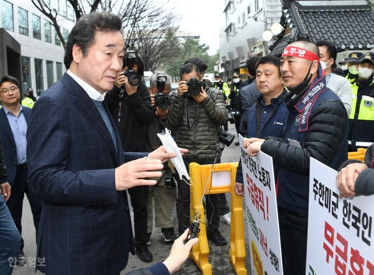 Lee Nak-yon, left, a former prime minister, talks with members of the USFK Korean Employees Union in front of the ruling Democratic Party of Korea's building in Yeouido, Seoul, March 27, during the union's protest ahead of a planned furlough of Korean workers due to an absence of defense-cost sharing deal. / Korea Times file