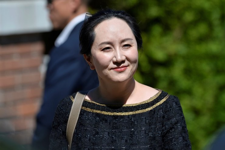 Huawei's chief financial officer Meng Wanzhou smiles as she leaves her home to attend a court hearing in Vancouver, British Columbia, Canada, May 27, 2020. Reuters
