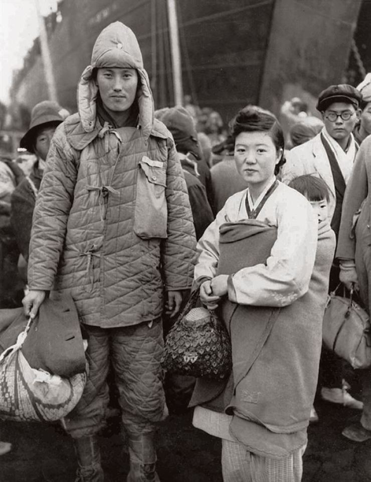 A young couple poses near an unidentified U.S. vessel in the North Korean port city of Hungnam in December 1950. Some 100,000 North Koreans were successfully evacuated in U.S. cargo ships. / Courtesy of Noonbit Publishing