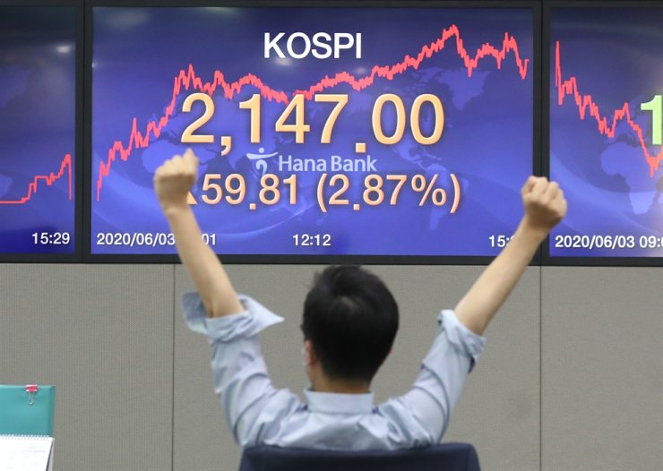 A dealer stretches in front of a monitor at a dealing room at Hana Bank headquarters in Seoul, Wednesday, as the KOSPI closed at 2,147 points, up 2.87 percent from the previous closing. / Yonhap