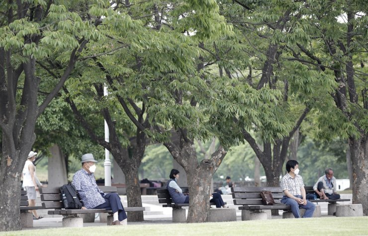 Visitors wearing face masks to prevent the spread of the new coronavirus sit on benches while maintaining social distancing at a park in Seoul, Saturday, June 20, 2020. AP