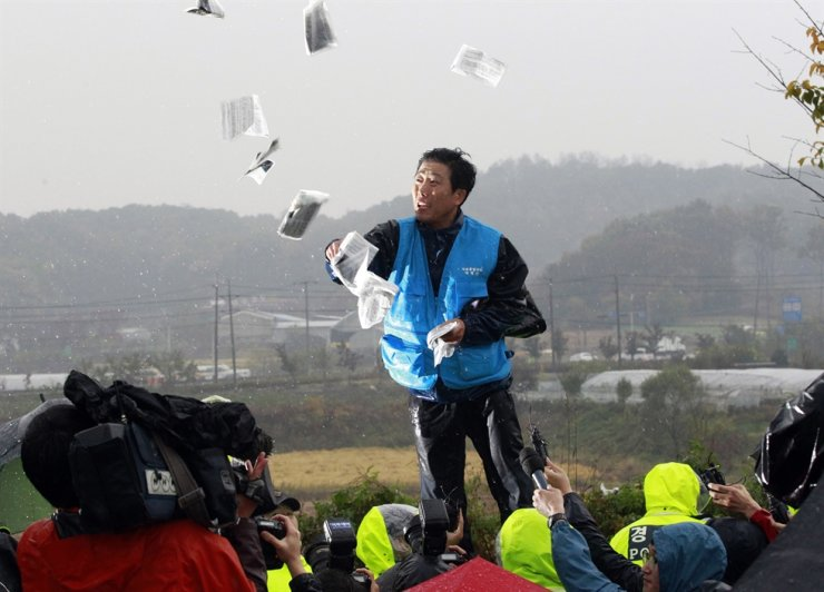 In this Oct. 22, 2012, file photo, Park Sang-hak, a North Korean refugee who launched balloons carrying propaganda balloons toward North Korea for years, hurls anti-North Korea leaflets as police block his planned rally on a road in Paju near demilitarized zone, South Korea. South Korea's police on Friday, June 26, 2020 raided the office of an activist whose anti-Pyongyang leafleting campaign has recently intensified tensions with North Korea. (AP Photo/Ahn Young-joon, File)