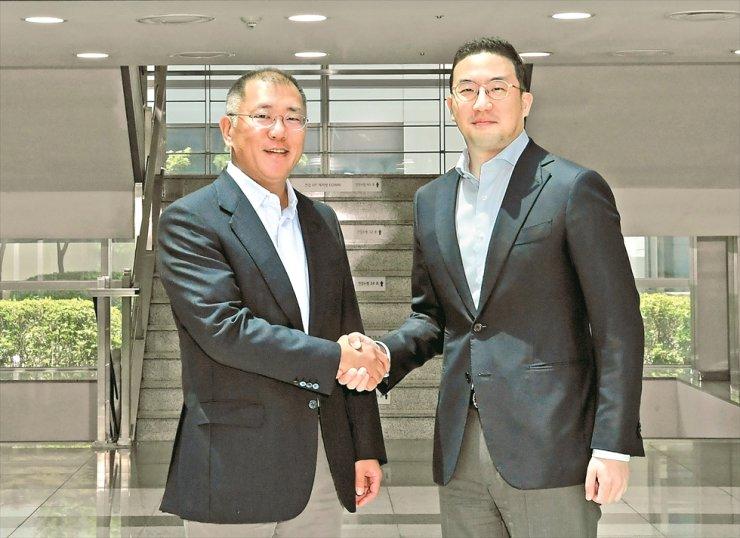 LG Group Chairman Koo Kwang-mo, right, shakes hands with Hyundai Motor Group Executive Vice Chairman Chung Euisun at LG Chem's Ochang plant in North Chungcheong Province, Monday. / Courtesy of LG Corp.