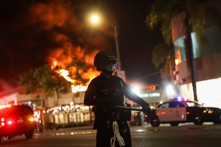 A law enforcement officer takes position as a building burns during nationwide unrest following the death in Minneapolis police custody of George Floyd, in Los Angeles, California, May 30, 2020. Reuters