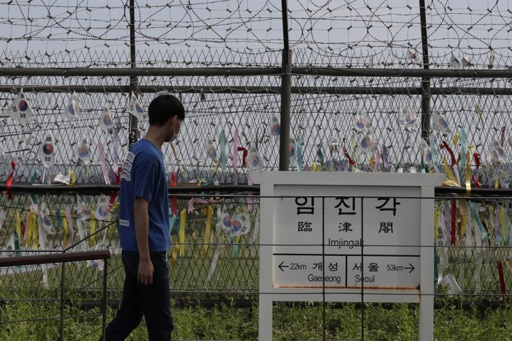 A visitor walks in front of a sign showing the distance to the North Korean city of Gaeseong and the South Korean capital of Seoul near a wire fence decorated with ribbons written with messages wishing for unification of the two Koreas at the Imjingak Pavilion in Paju, Gyeonggi Province, Sunday. / AP-Yonhap