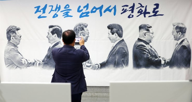 A placard depicting three inter-Korean summits in 2000, 2007 and 2018 is hung outside a meeting room at the National Assembly in Seoul, Monday, the 20th anniversary of a
