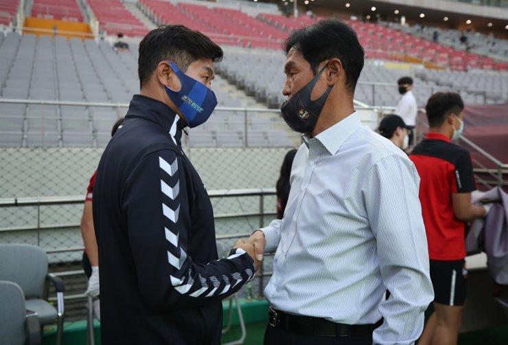 FC Seoul head coach Choi Yong-soo, right, shakes hands with Ulsan Hyundai head coach Kim Do-hoon before the two teams' K League 1 match at the Seoul World Cup Stadium, Saturday. / Yonhap