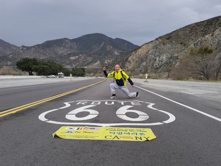 Ven. Jino on America's Route 66 poses with a banner for his fundraising marathon that bears the flags of South Korea, the United States and the symbol of People Making Dreams Come True, a philanthropic establishment he founded to help migrant workers in Korea. Courtesy of People Making Dreams Come True