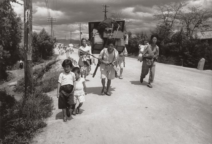 Korean War refugees walk down the road in Daejeon City in this 1950 photo.  / Courtesy of Noonbit Publishing