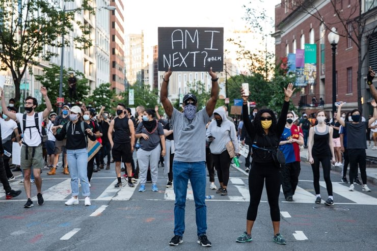 Demonstrators hold signs as they protest the death of George Floyd at the hands of Minneapolis Police in Washington, D.C. on May 31, 2020. - Thousands of National Guard troops patrolled major US cities after five /AFP