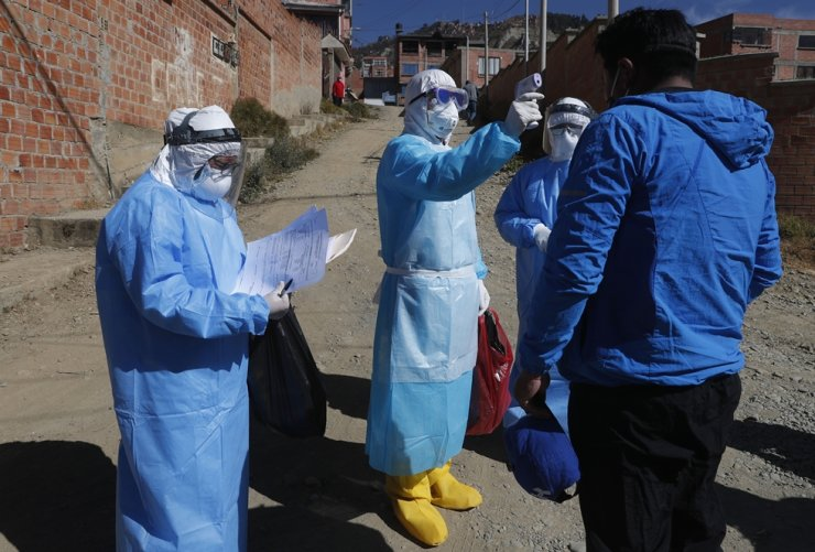 A doctor dressed in full protective gear measures the temperature a man during a house-to-house coronavirus testing drive in Villa El Rosal, on the outskirts of La Paz, Bolivia, Sunday, July 12, 2020. (AP Photo/Juan Karita)