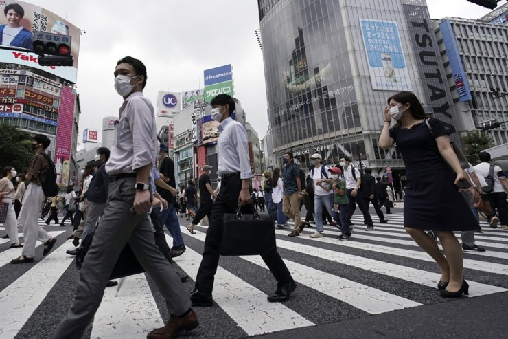 People wearing masks against the spread of the new coronavirus walk at Shibuya pedestrian crossing in Tokyo, Friday. / AP-Yonhap