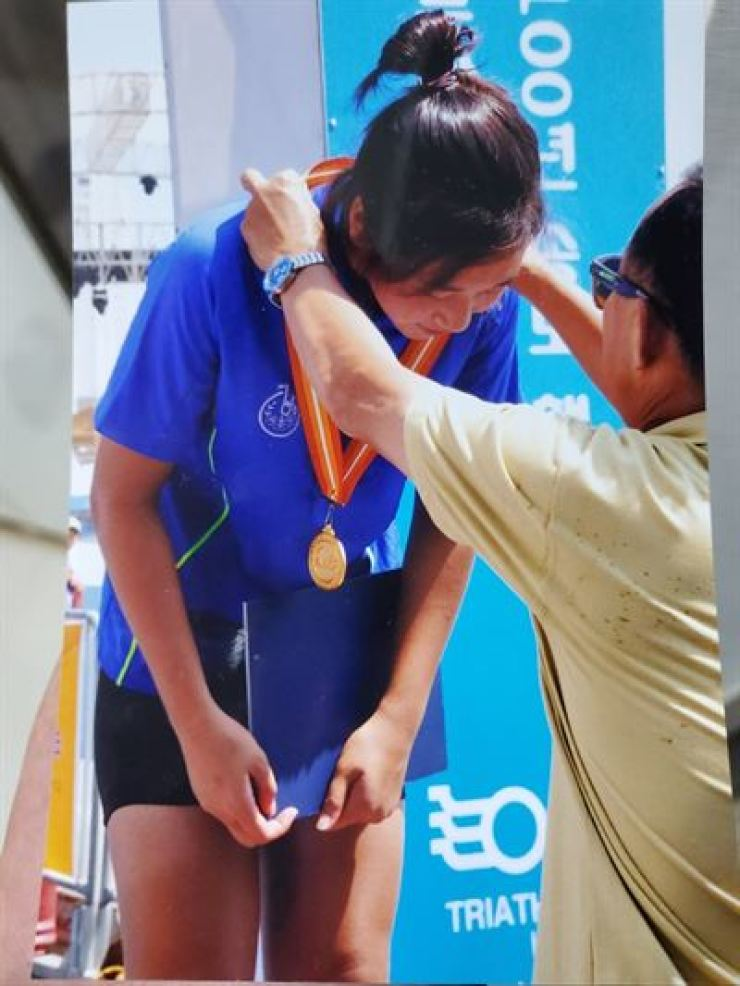 The late triathlete Choi Suk-hyeon receives a gold medal at the 2013 National Martine Sports Games in Ulsan, South Gyeongsang Province, in the photo provided by her family on July 2, 2020. Yonhap