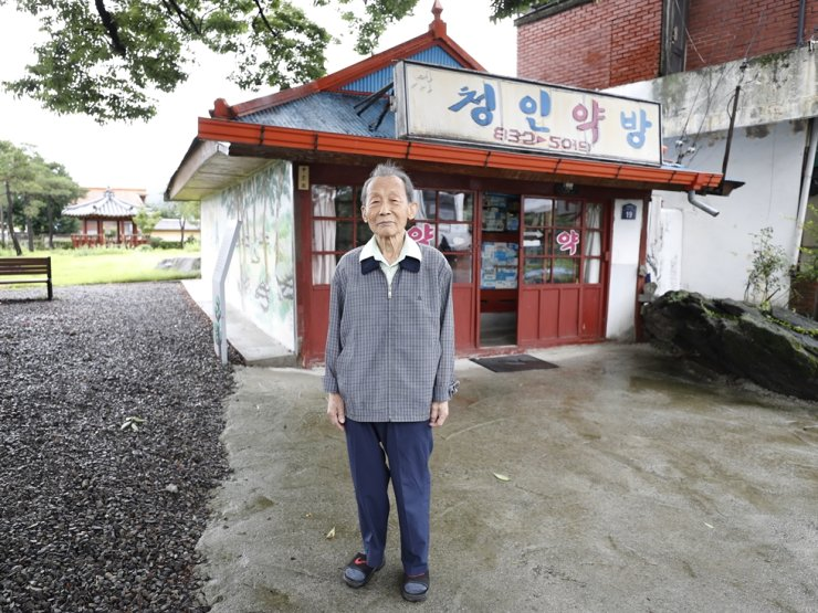 Shin Jong-chul, 88, poses for a photo in front of Chungin Pharmacy which he has operated for more than 60 years in Goesan, North Chungcheong Province. / Courtesy of Goesan County Office