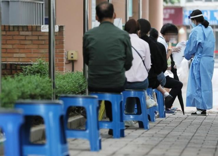 People wait for coronavirus tests at a makeshift clinic in Seoul, in this June 30 photo. Yonhap