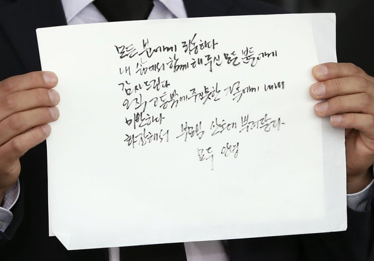 A Seoul City official holds the handwritten will of Park in front of the funeral house, Friday. Yonhap
