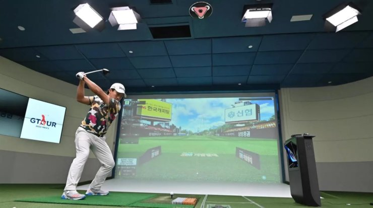 A South Korean golfer hits in a simulation booth during the GTour screen golf tournament in Daejeon, south of Seoul?Jung Yeon-je AFP