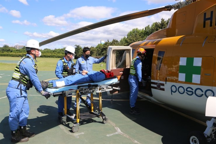 Emergency medical technicians at POSCO take part in an emergency patient transportation drill using a helicopter at the company's mill in Pohang, May 20. Courtesy of POSCO