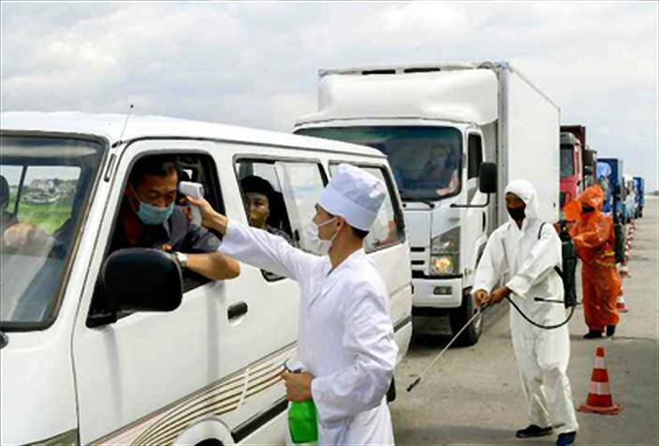 A picture of a quarantine official measuring drivers' temperatures with an infrared thermometer was printed in North Korea's state-run newspaper Rodong Sinmun, July 31, amid the regime's declaration of a national emergency in response to COVID-19. / Yonhap