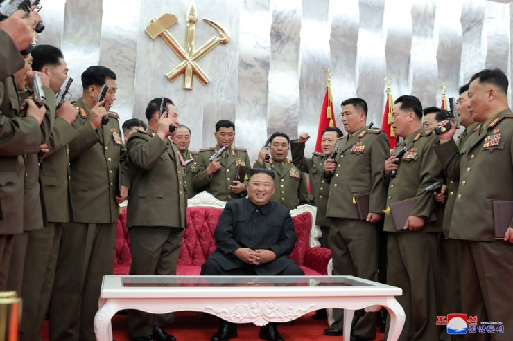 North Korean leader Kim Jong-un, center, smiles with leading commanding officers of the country's armed forces after he gave them