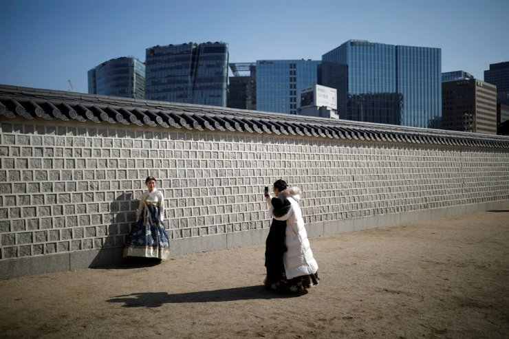 A tourist wearing hanbok poses for a photo at Gyeongbok Palace in central Seoul in this Feb. 11, 2019, file photo. Reuters