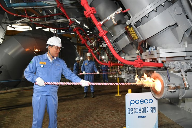 POSCO Chairman Choi Jeong-woo lights the steelmaker's No. 3 blast furnace at its steel mill in Gwangyang, South Jeolla Province, Friday. The company restarted steel production at the blast furnace after completing maintenance work. / Courtesy of POSCO