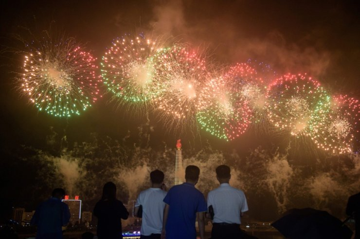 In a photo taken on July 27, 2020, people watch a firework display before the Juche tower on the occasion of 67th anniversary of the signing of the Korean War armistice agreement in Pyongyang. AFP