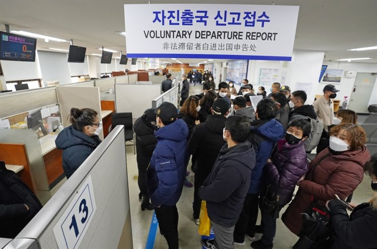 In this March 6, 2020, file photo, undocumented immigrants stand in line to fill out departure cards at the Korea Immigration Service's office in western Seoul. Yonhap
