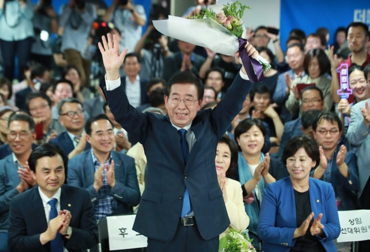 Park Won-soon raises up bouquet after winning his third term for Seoul mayoral election in this 2018 file photo. Yonhap