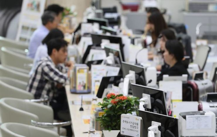 People seeking to take out loans sit in front of tellers at a bank in Seoul, in this file photo. Korea Times file