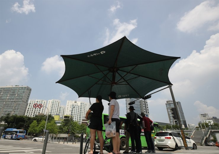 People wait for a green light under a sun shelter in Seoul, Thursday. Temperatures in the capital reached 34 degrees Celsius in the afternoon. Yonhap