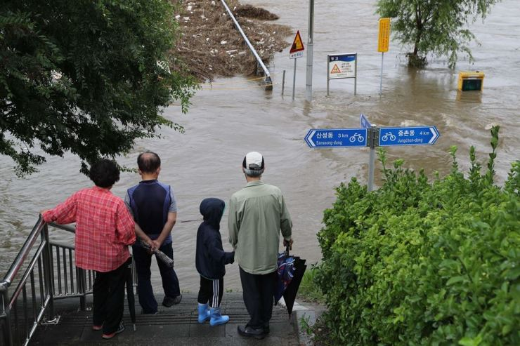 A flooded stream in Daejeon has stopped passers-by as the city saw downpour on Monday that continued from a day before. Yonhap