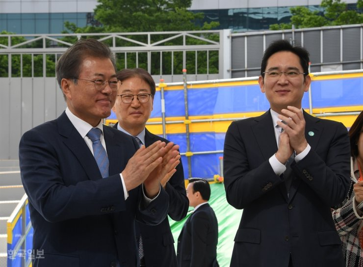 President Moon Jae-in, left, takes a tour of Samsung Electronics' semiconductor production plant in Hwaseong, Gyeonggi Province, April 30, 2019, while accompanying the group's leader Lee Jae-yong, right, and Yoon Boo-keun, center, the-then vice chairman of the company. / Korea Times file