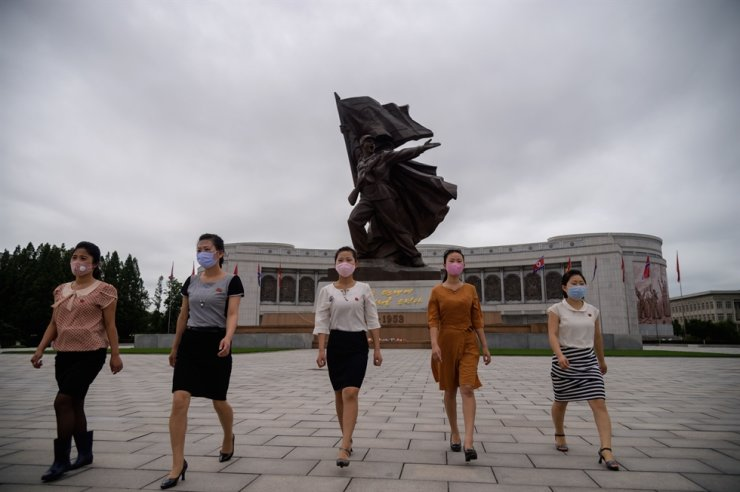 People wearing face masks walk away after paying their respects before a sculpture entitled 'Victory' at the Victorious Fatherland Liberation War Museum on the occasion of 67th anniversary of the signing of the Korean War armistice agreement in Pyongyang, July 27, 2020. AFP