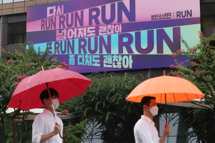 A large banner featuring the lyrics of BTS' 'Run,' the lead song of the boy band's album 'The Most Beautiful Moment in Life, Pt. 2,' is installed on the exterior of the Kyobo Building at Gwanghwamun in central Seoul, Aug. 19. It reads, 'Run, run, run again. It's OK if you fall. Run, run, run again. It's OK to get hurt.' / Korea Times file